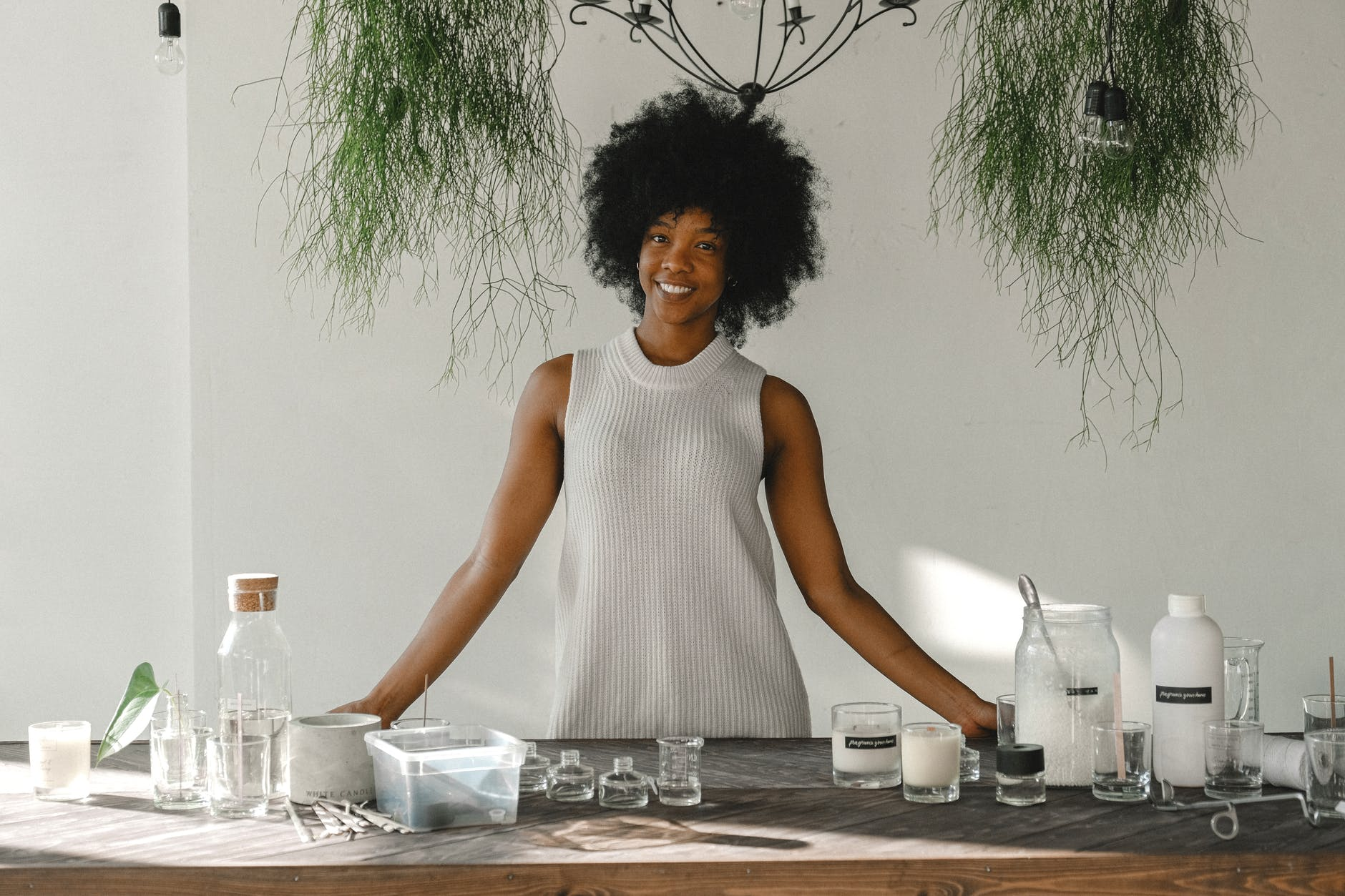 delighted black woman standing at table in workshop for making candles